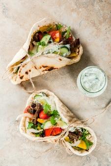 Lanche saudável, almoço. giroscópios de sanduíche envoltos em grego tradicional - tortilhas, pão árabe com recheio de legumes, carne e molho de carne tzatziki