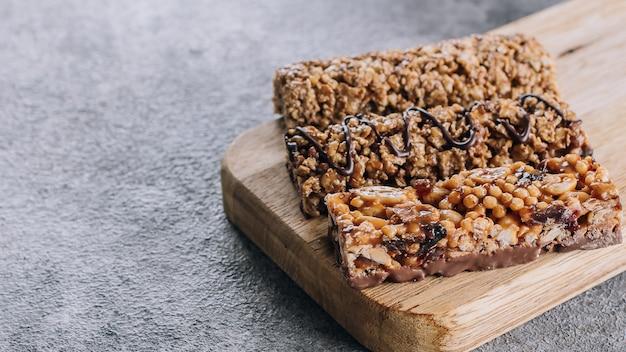 Lanche saudável. barra de granola. barra de granola do cereal com porcas, chocolate na placa de madeira.