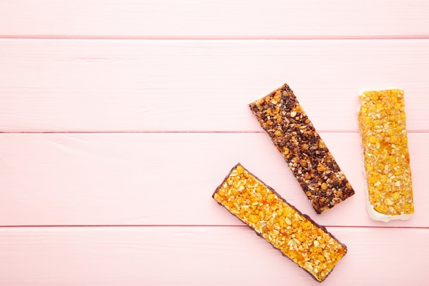 Lanche saudável, barras de cereais com passas e frutas secas em um fundo rosa