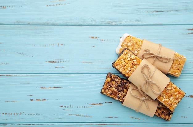 Lanche saudável, barras de cereais com passas e frutas secas em uma parede azul