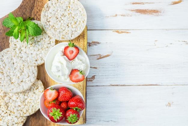 Lanche saudável de bolos de arroz com ricota e morangos