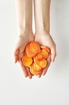 Lanche saudável de cenoura seca em mãos isoladas