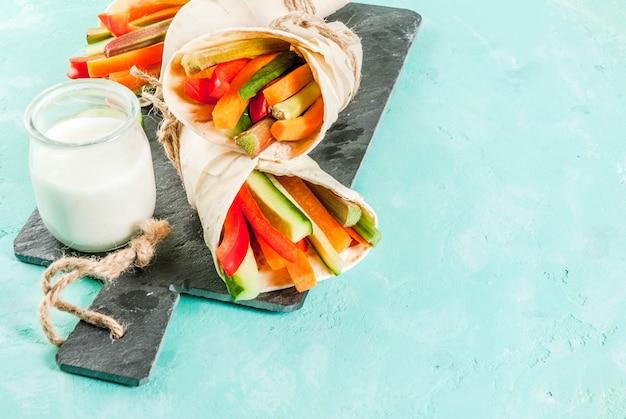 Lanche saudável de verão, sanduíche de tortilha de estilo mexicano envolve sortidas varas coloridas de legumes frescos (aipo, ruibarbo, pimenta, pepino e cenoura) com molho de iogurte mergulham fundo azul claro