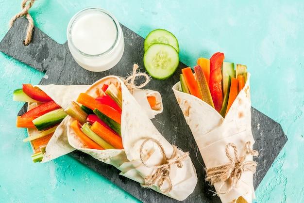 Lanche saudável do verão, sanduíche de tortilla de estilo mexicano envolve varas coloridas de legumes frescos variadas (pepino e pimenta de aipo com ruibarbo e aipo) com molho de iogurte, mergulho - fundo azul claro