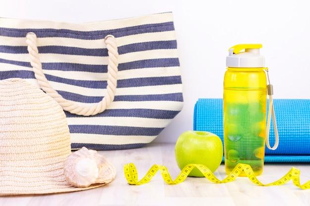 Lanche saudável, fita métrica e garrafa de água sobre uma superfície de madeira clara. preparação para a temporada de verão e a praia, bolsa de praia, chapéu e conchas, perda de peso e conceito de esportes
