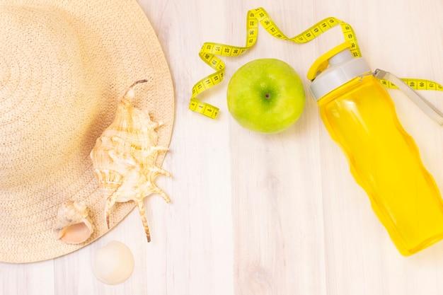 Lanche saudável, fita métrica e garrafa de água sobre uma superfície de madeira clara. preparação para a temporada de verão e a praia, chapéu e conchas, perda de peso e conceito de esportes