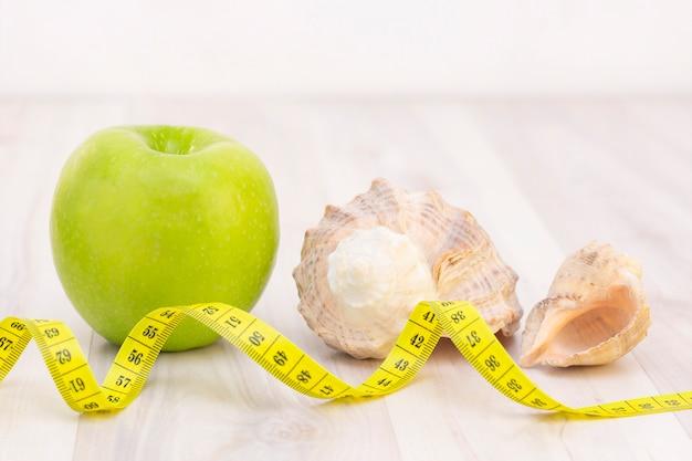 Lanche saudável, fita métrica sobre uma superfície de madeira clara. preparação para a temporada de verão e o conceito de praia, conchas, perda de peso e esportes