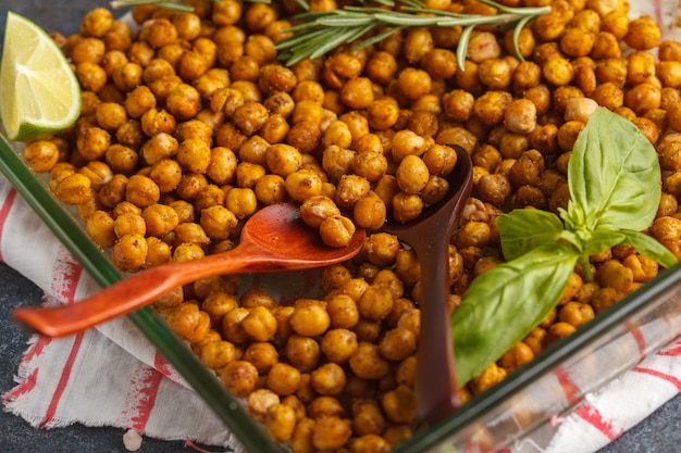 Lanche saudável - grão-de-bico picante assado em um prato de vidro. conceito de comida vegana saudável.