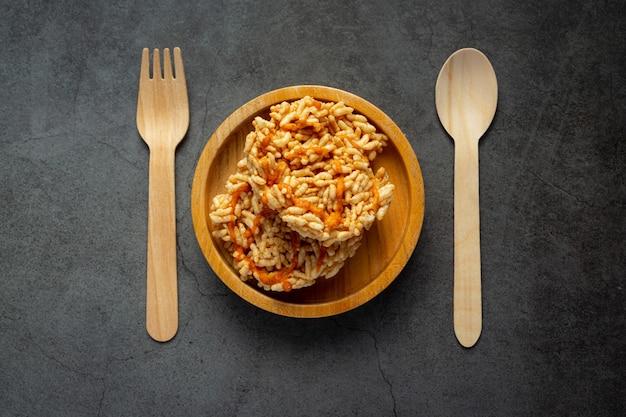 Lanche tailandês; kao tan ou biscoito de arroz em uma tigela de madeira com colher de pau e garfo