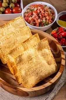 Lanche típico brasileiro chamado pastel. acompanha vinagrete e pimenta em mesa de madeira