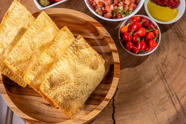 Lanche típico brasileiro chamado pastel. acompanha vinagrete e pimenta
