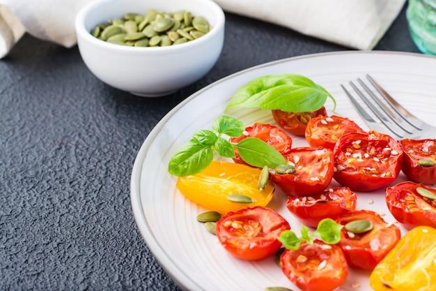 Lanche vegetariano de dieta. tomates secos ao sol com manjericão, sementes de gergelim e abóbora em um prato em um fundo preto. fechar-se. copie o espaço
