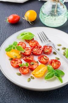 Lanche vegetariano de dieta. tomates secos ao sol com manjericão, sementes de gergelim e abóbora em um prato em um fundo preto. visão vertical