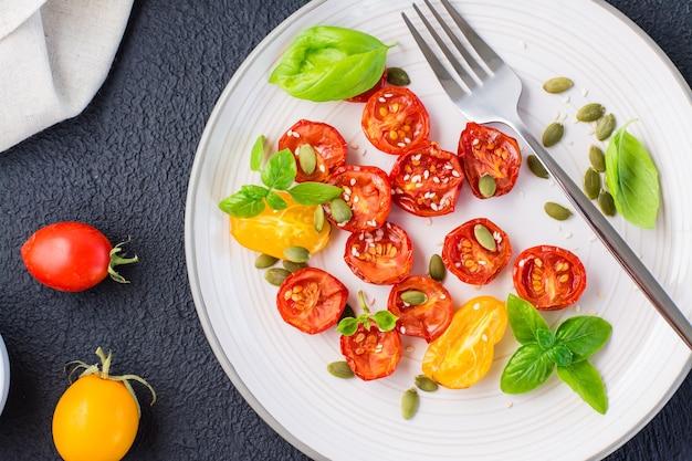 Lanche vegetariano de dieta. tomates secos ao sol com manjericão, sementes de gergelim e abóbora em um prato em um fundo preto. vista do topo. fechar-se