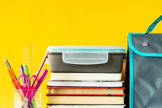 Lancheira com comida fica em uma pilha de rei ao lado de um copo com canetas e lápis e um saco para o almoço