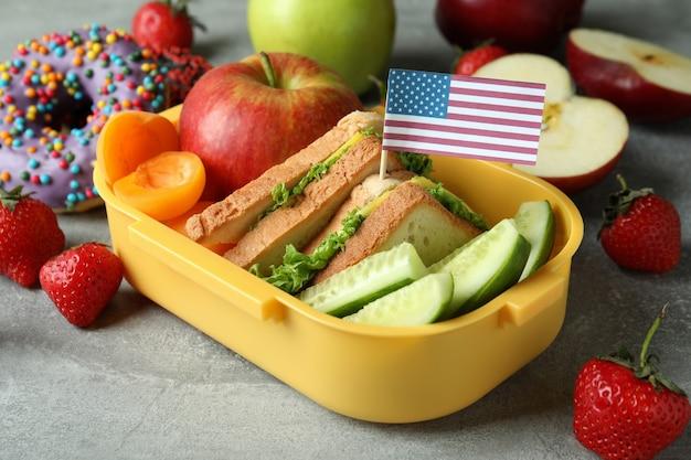 Lancheira com comida saborosa e bandeira americana em plano de fundo texturizado cinza