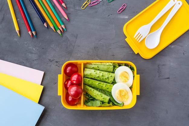 Lancheira com comida saudável e material escolar em cinza
