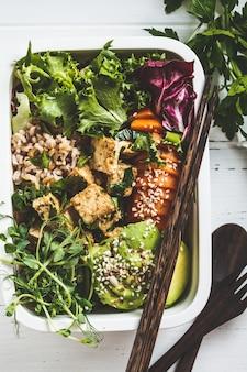 Lancheira com comida vegetariana saudável. caixa de bento com arroz, batata doce, tofu e legumes.