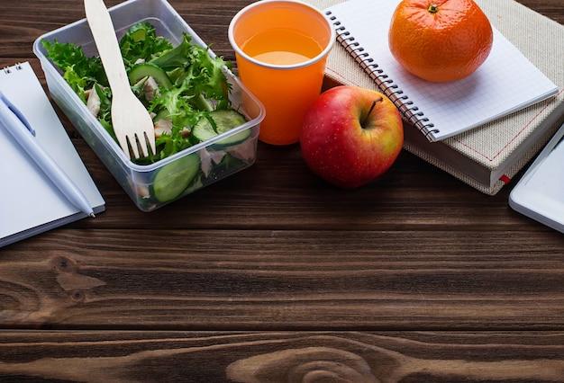Lancheira com salada, maçã, tangerina e suco.