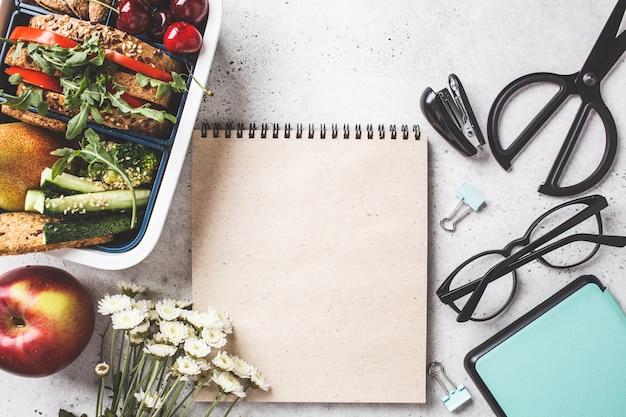 Lancheira com sanduãche, frutas, lanches, caderno, lã¡pis e itens de escola, vista de cima.