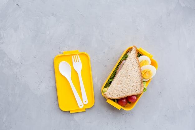 Lancheira com sanduíche e produtos diferentes em cinza