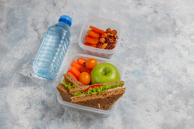 Lancheira com sanduíche, legumes, frutas em branco.