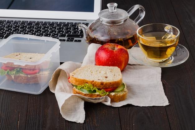 Lancheira com sanduíches de salada de frango. frutas e chá no fundo do local de trabalho