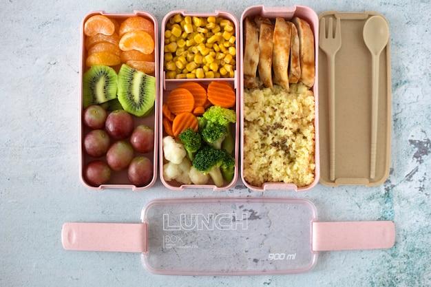 Lancheira com vista superior de refeição fresca. mingau, frango, salada, frutas