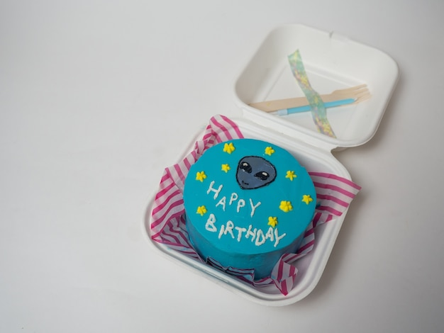 Lancheira de bolo coreano, bolo com a inscrição feliz aniversário e o rosto de um alienígena. lugar para o seu texto
