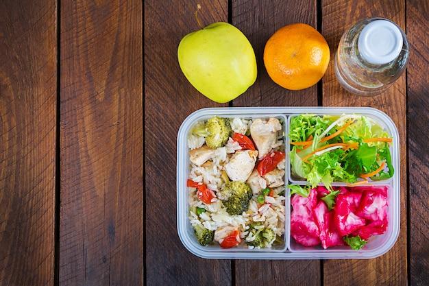 Lancheira de frango, brócolis, ervilha, tomate com arroz e repolho roxo. comida saudável. leve embora. lancheira. vista do topo