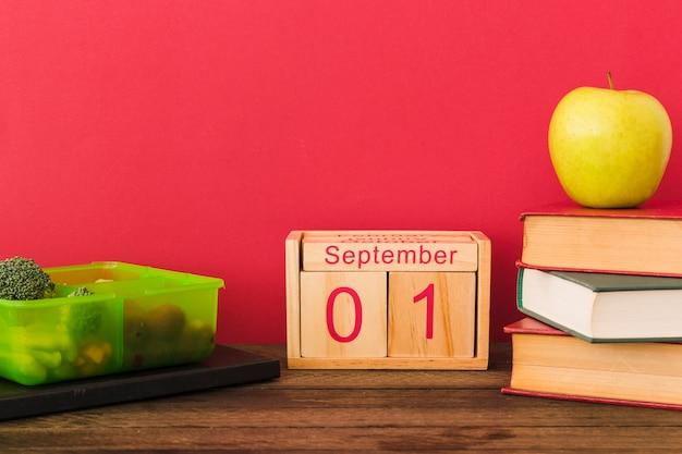 Lancheira e calendário perto de frutas e livros