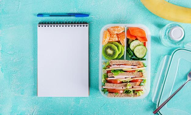 Lancheira escolar com sanduíche, legumes, água e frutas na mesa.