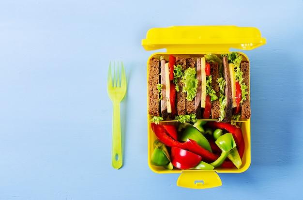 Lancheira escolar saudável com sanduíche da carne e legumes frescos no fundo azul.