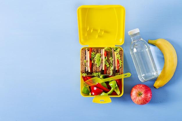 Lancheira escolar saudável com sanduíche de carne e legumes frescos, garrafa de água e frutas na mesa azul. vista do topo. configuração plana