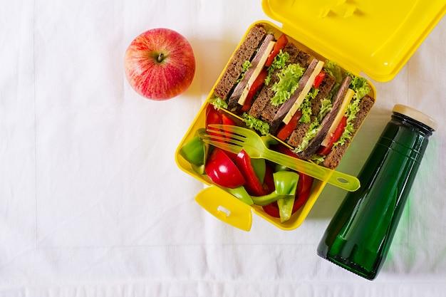 Lancheira escolar saudável com sanduíche de carne e legumes frescos, garrafa de água e frutas na mesa branca. vista do topo. configuração plana