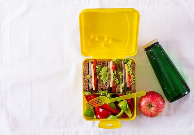 Lancheira escolar saudável com sanduíche de carne e legumes frescos, garrafa de água e frutas na mesa branca.