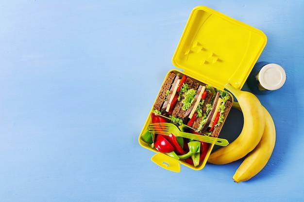 Lancheira escolar saudável com sanduíche de carne e legumes frescos, garrafa de água e frutas sobre fundo azul.