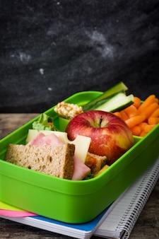 Lancheira escolar saudável: sanduíche, legumes, frutas e suco na mesa de madeira