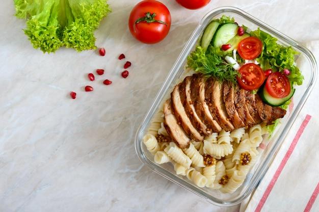 Lancheira: rotini com peito de frango assado e salada. vista superior, plana leigos. delicioso almoço saudável.