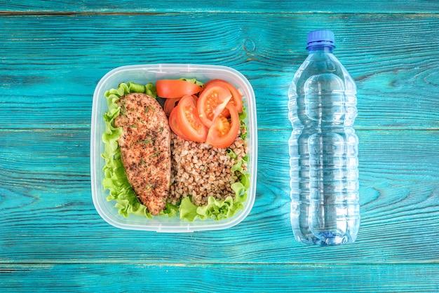 Lancheira saudável com peito de frango grelhado, trigo sarraceno e tomate e garrafa de água sobre fundo azul de madeira.