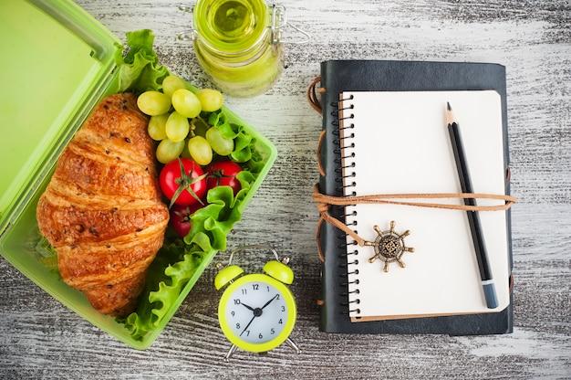 Lancheira verde com lanche e um notebook