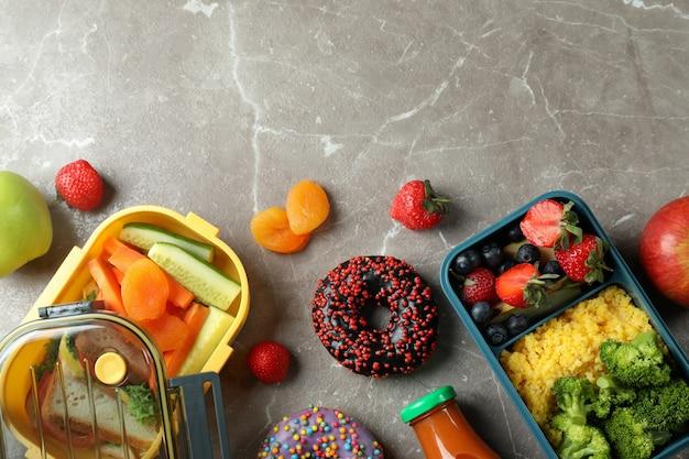 Lancheiras com comida saborosa em mesa texturizada cinza