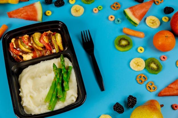 Lancheiras com purê de batatas e legumes prontos para o trabalho ou escola.