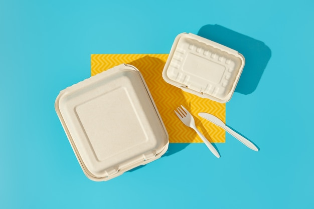 Lancheiras e talheres na mesa colorida. conceito de entrega de comida plana leigos