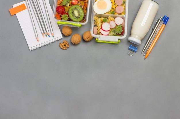 Lancheiras nutritivas com frutas, vegetais, nozes e papelaria colorida.