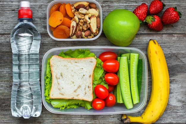 Lancheiras saudáveis com sanduíche e legumes frescos, garrafa de água, nozes e frutas