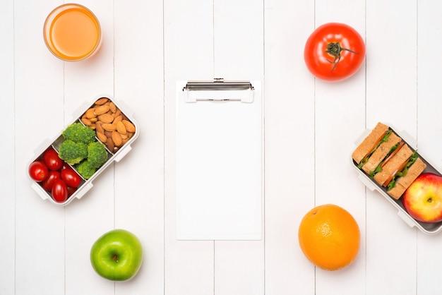 Lancheiras saudáveis com sanduíche, legumes frescos, frutas e nozes em fundo branco de madeira. vista de cima