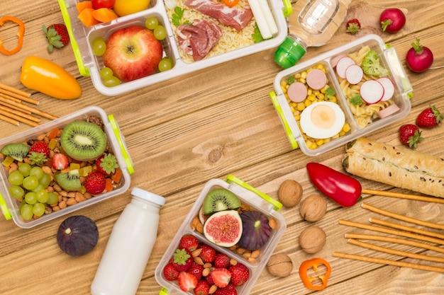 Lancheiras saudáveis e equilibradas com conjunto de frutas, frutas, vegetais e presunto