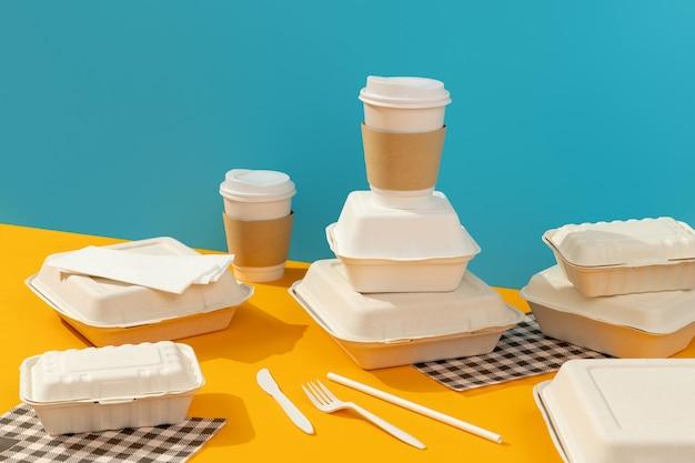 Lancheiras, talheres e bebidas na mesa laranja. conceito de entrega de comida