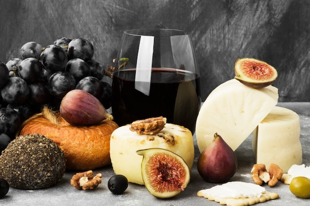 Lanches com vinho - vários tipos de queijos, figos, nozes, mel, uvas em um fundo cinza